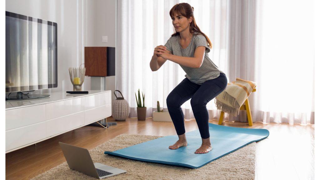 Donna che fa ginnastica in casa; consigli per lavorare in smart working e non avere freddo