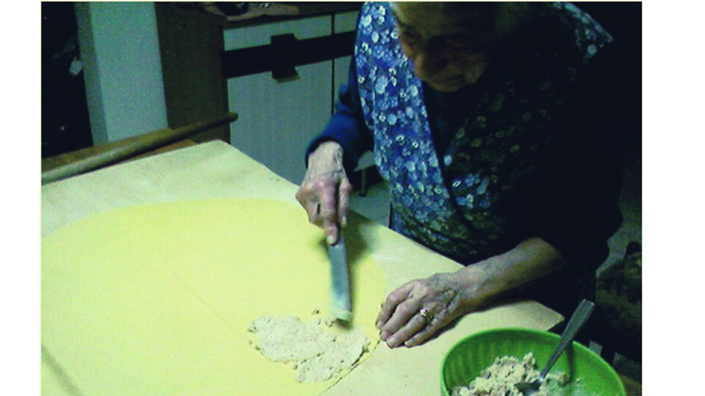 Una nonna molto anziana, ma comunque ancora azdora romagnola, con la tipica veste da cucina romagnola, che spalma il ripieno sulla sfoglia all'uovo per fare la pasta ripiena