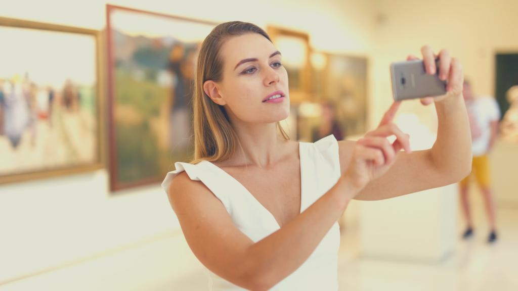 foto di giovane donna in un museo che fa una foto col cellulare