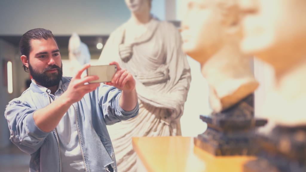 Riapertura musei in Romagna: un giovane uomo con la barba fotografa dei mezzi busti antichi