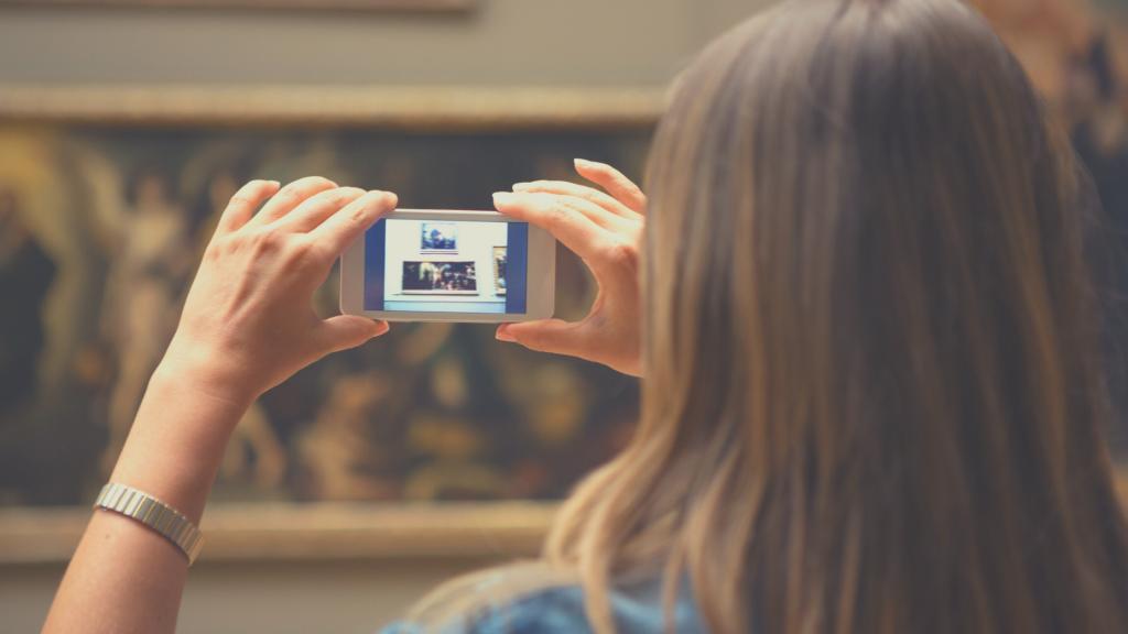 giovane donna fotografata di spalle mentre fotografa col cellulare un quadro. Musei aperti in Emilia Romagna