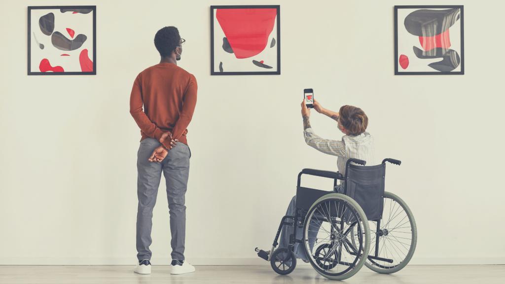 un giovane uomo con disabilità motoria, in sedia a rotelle, fotografa un quadro. Accanto a lui un uomo in piedi. entrambi fotografati di spalle