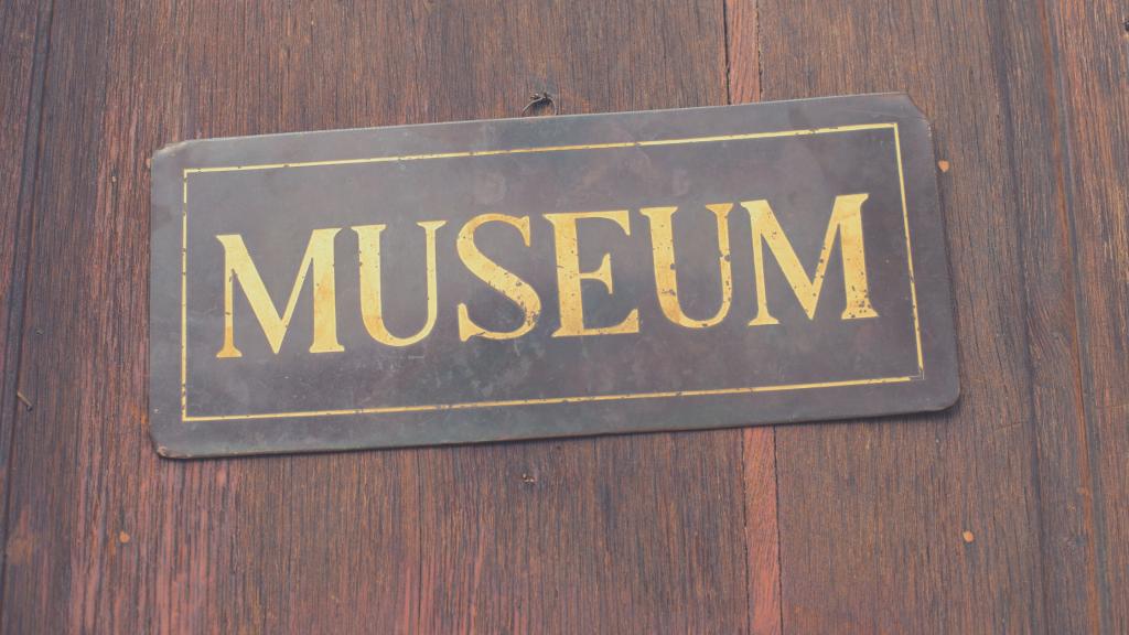 targa su porta con scritto MUSEUM. Musei aperti in Emilia Romagna