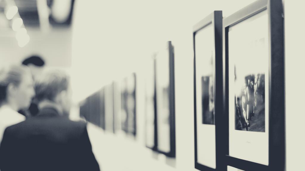 una foto in bianco e nero con un corridoio museale ed osservatori