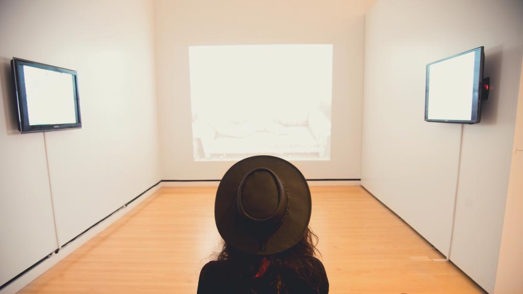 Una giovane donna fotografata di spalle mentre osserva un quadro