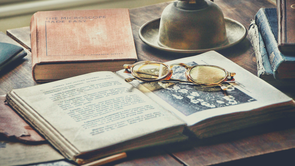 fotografia di un polveroso libro antico, aperto, cui sono appoggiati sopra antichi occhiali da vista