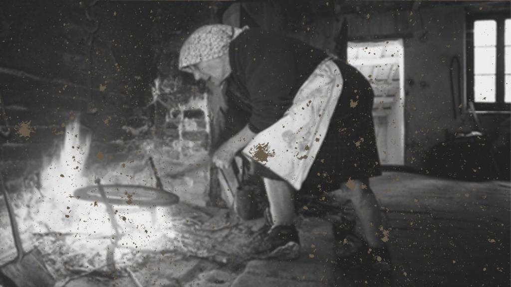 Storia della piadina romagnola: nella foto storica una azdora al focolare cuoce la piadina sulla graticola