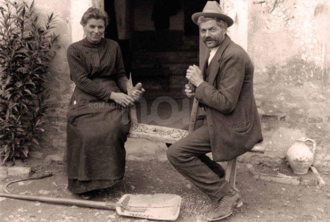 Azdore e azdora romagnola seduti davanti alla misera porta di casa. Foto deglil anni 30