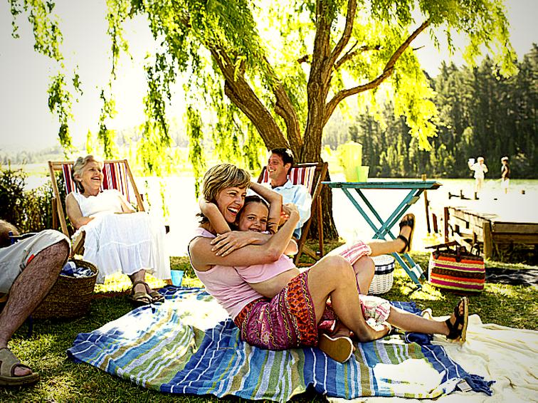 Foto di una famiglia sull'erba vicino ad un acquitrino. Per godere al meglio le vacanze sul Delta del Po è importante proteggersi dalle zanzare