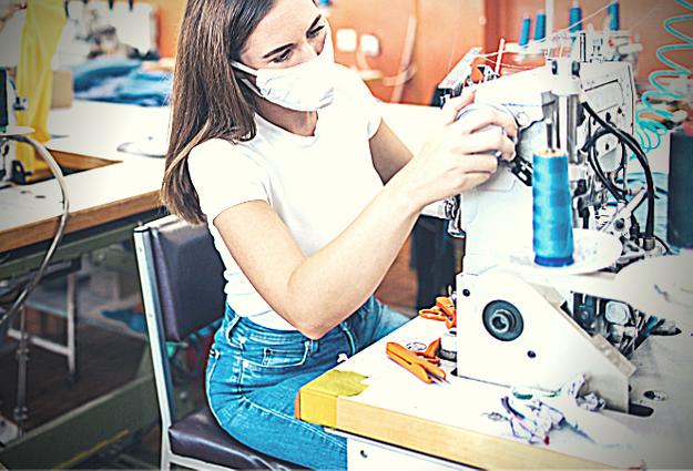 Una ragazza ad una macchina da cucire: l'intimo artigianale è una scelta etica e di sostenibilità