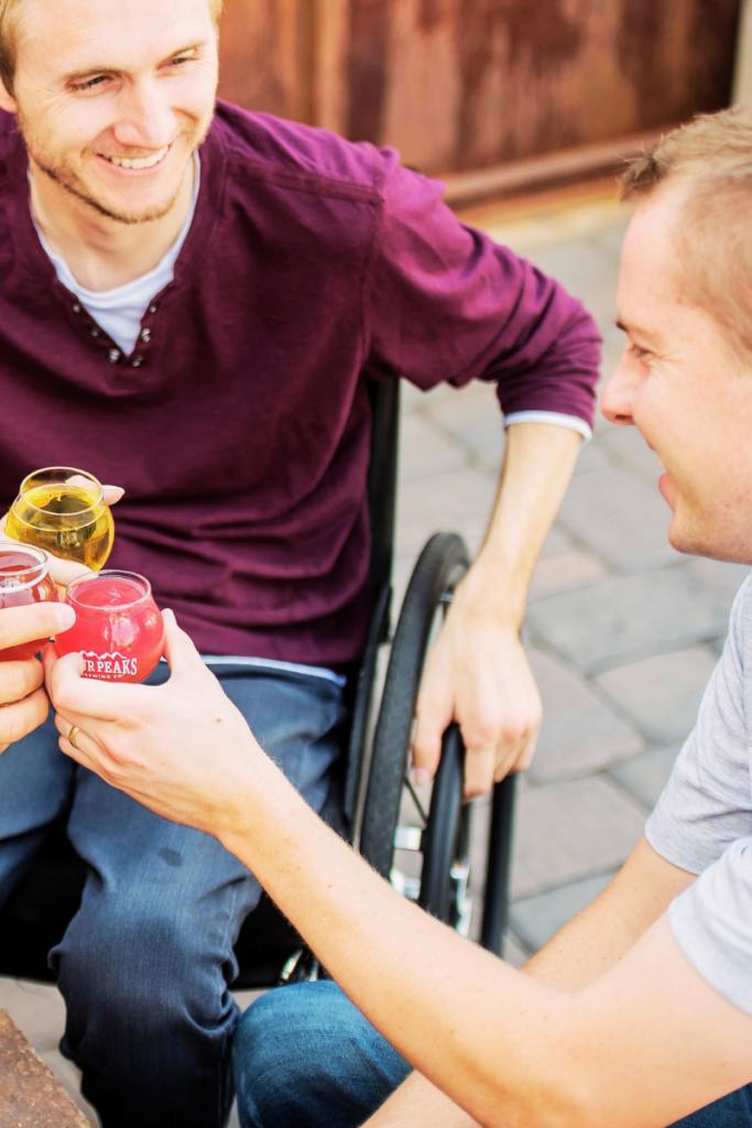 ragazzo su sedia a rotelle brinda con gli amici è l'immagine perfetta per rappresentare le vacanze in Romagna per persone con disabilità