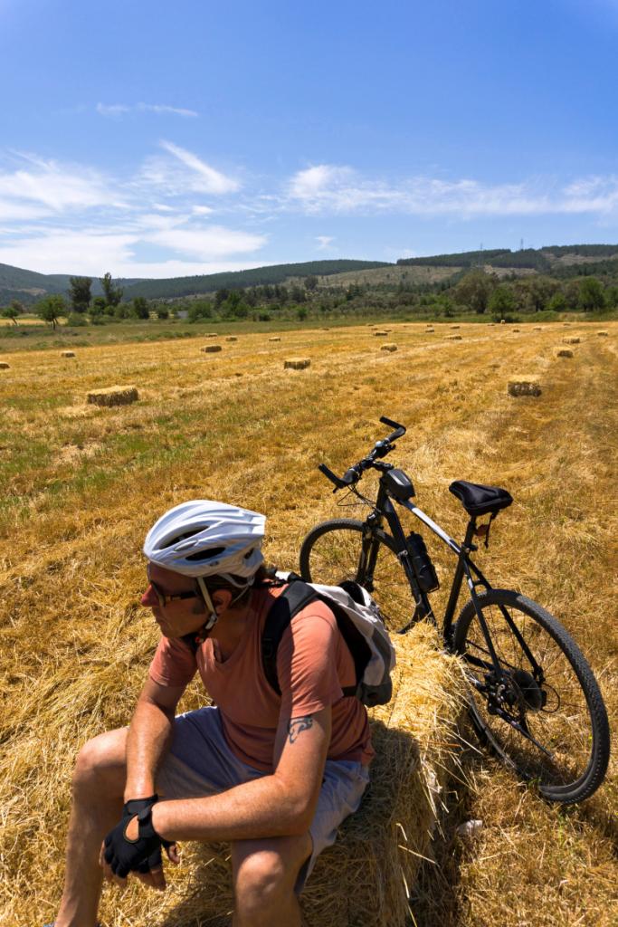 un ciclista si riposa su una balla di fieno, il cicloturismo e ciclovie in Romagna sono molto diffusi per le vacanze in Romagna