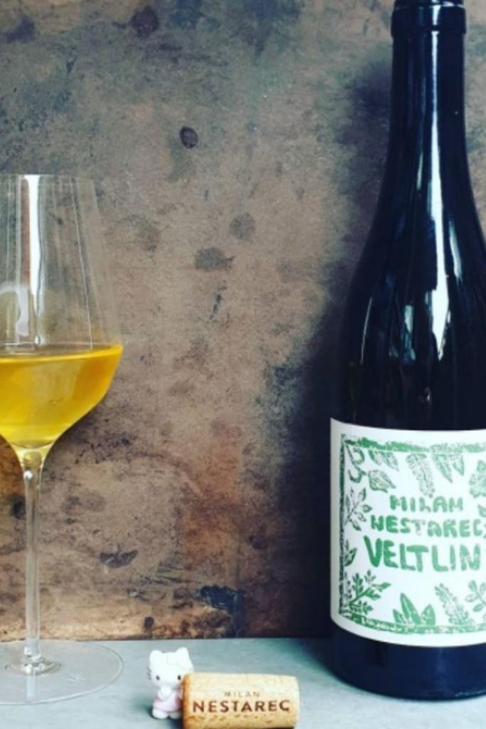 Bottiglia e bicchiere di vino naturale venduto presso la vineria Coramella di Brisighella presso cui i titolari sapranno spiegarti come si faccia a produrre vino naturale