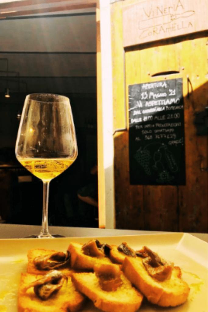 Dettaglio di un calice di vino bianco naturale e crostini di pane con sopra acciughe sott'olio, proposte di punta della Vineria coramella di Brisighella