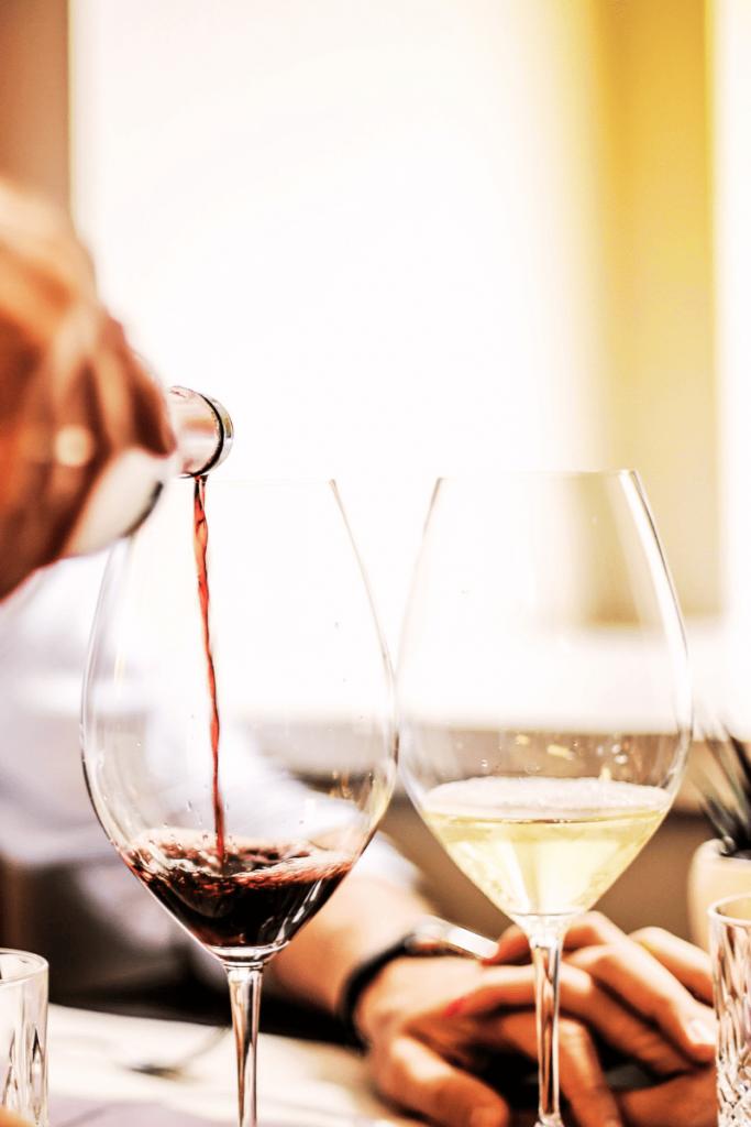 Bere naturale in Romagna, foto di un cameriere che versa vino in un calice al ristorante. Ambiente elegante