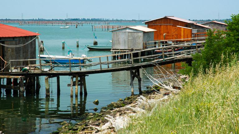 Gli itinerari in moto in Romagna nel Delta del Po portano a questi scorci bellissimi di acquitrini e capanni da pesca colorati.
