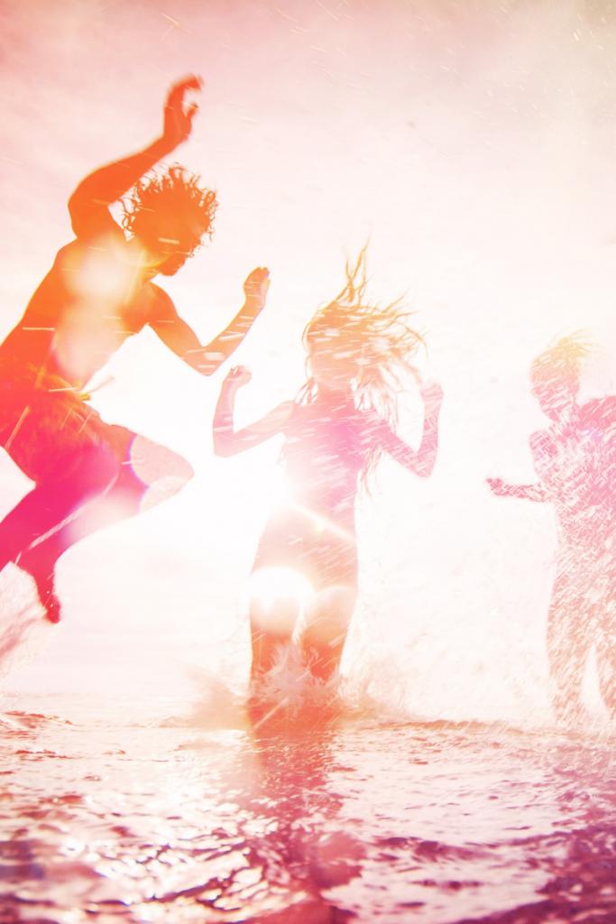 gruppi di giovani, in controluce, che saltano nell'acqua del mare