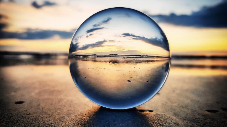 l'immagine al tramonto di una spiaggia romagnola vista attraverso una sfera