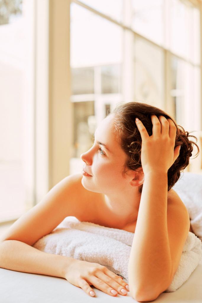 Una donna che si rilassa avvolta da morbidi asciugamani termali, magari nelle terme in Romagna e avendo approfittato del bonus terme 2021