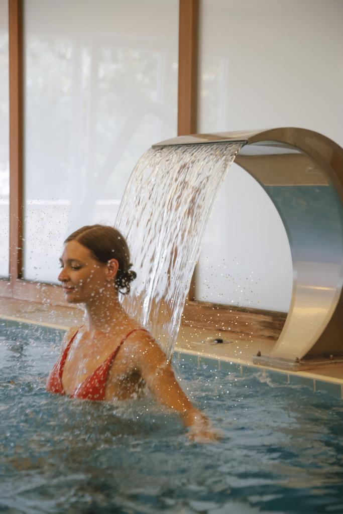 donna si rilassa sotto il getto d'acqua di una piscina termale, magari nelle terme in Romagna quindi in acqua salsobromoiodica e avendo approfittato del bonus terme 2021